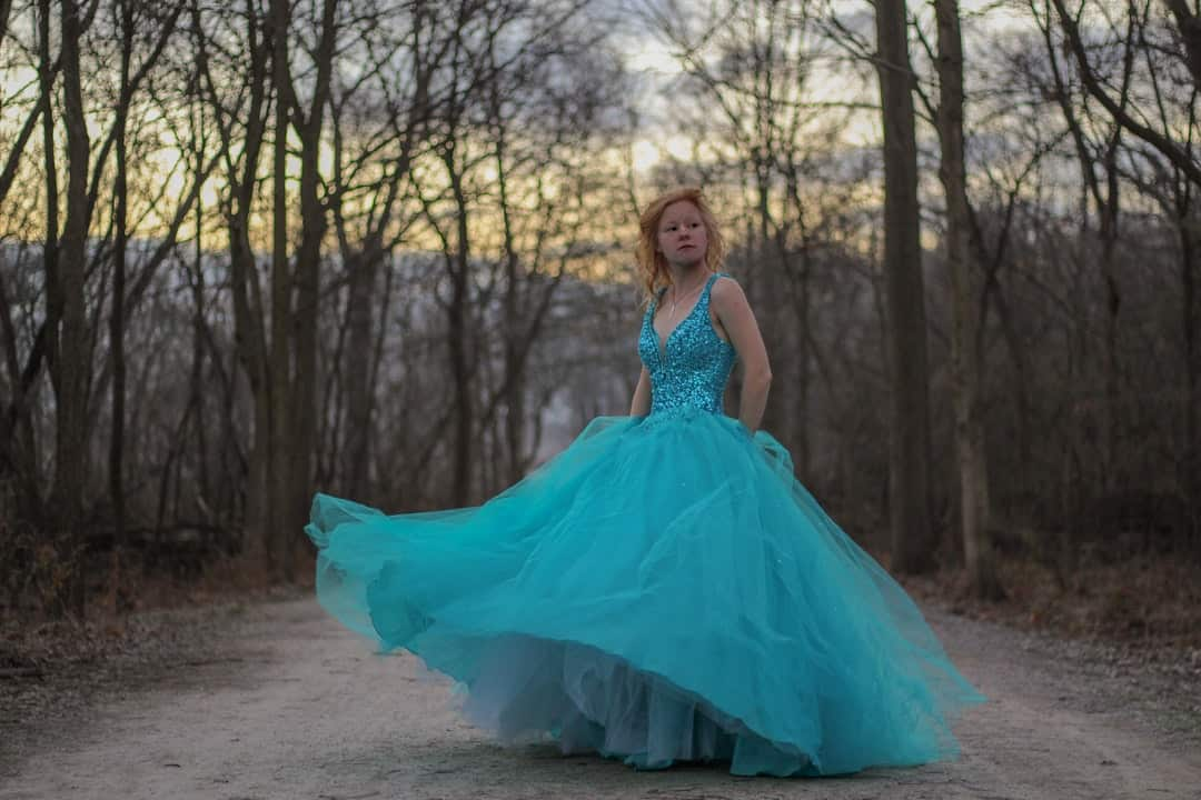 Janice Langbehn in a blue dress standing next to a forest